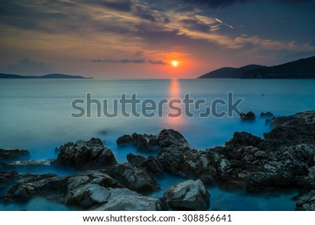 Rocky beach with calm sea during the sunset. Ocean on the blue hour