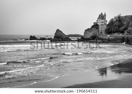 Rocky black and white, coastal beach seascape in Biarrtiz, France on the Atlantic ocean. Surfers in the water surfing waves towards a sandy beach. / Seascape in Biarrtiz, France. - stock photo