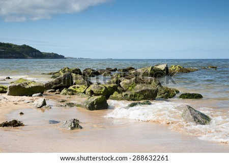 Rocky breakwater on beach at Bennlech Anglesey North Wales - stock photo