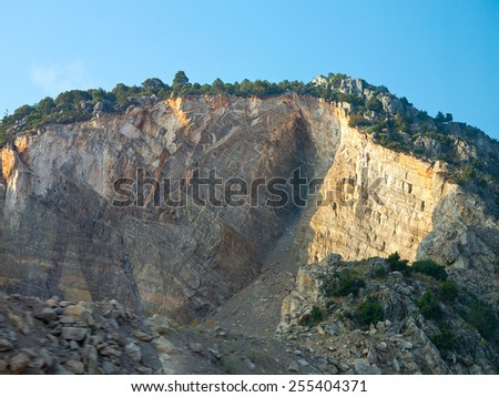 Rocky cliff, mountain trees and blue sky in sunset - stock photo