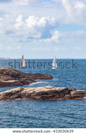 Rocky coast and sailing boats on the sea - stock photo