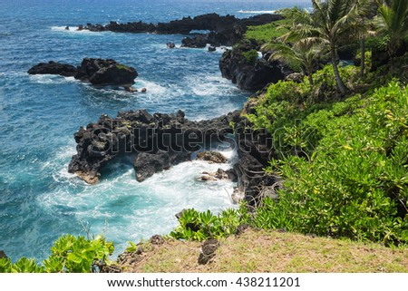 Rocky coast at Waianapanapa State Park. Some smaller sea arches can be seen. - stock photo