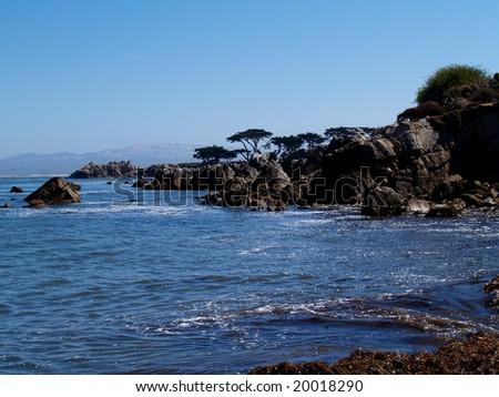 Rocky coast beneath a clear blue sky south of Santa Barbara, California - stock photo