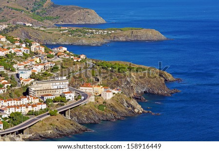Rocky coast in the Pyrenees Orientales with the village of Cerbere, Vermilion coast, Mediterranean sea, Roussillon, France - stock photo