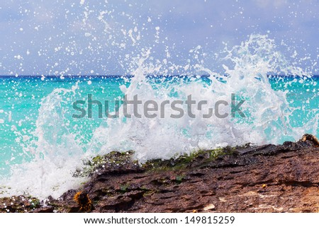 Rocky coast of Caribbean sea with splashing waves - stock photo