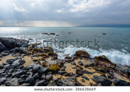 Rocky Coast - Stormy clouds coming over a rocky shore at north-west coast of Maui, with Molokai island in the background. Hawaii, USA. - stock photo