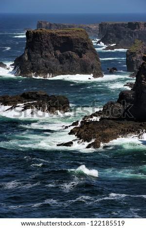 Rocky coast with cliffs and splashing water at Esha Ness. - stock photo