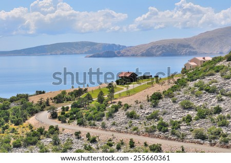 rocky coastal landscape of Croatia at the edge of a blue sea with some new houses - stock photo