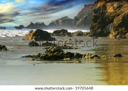 Rocky coastline and beach with dramatic sky and color - stock photo