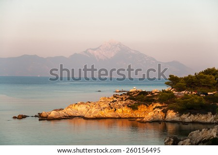Rocky coastline at sunset and mountain peak in the background - stock photo