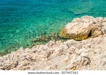 Rocky coastline beach and crystal clear blue sea on the coast of island Krk, Croatia, in the Adriatic sea at the Mediterranean - stock photo