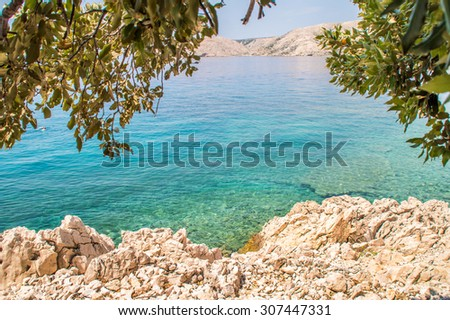 Rocky coastline beach and crystal clear blue sea on the coast of island Krk, Croatia, with some branches in a shade, Adriatic sea, Mediterranean, with islands in the background on a bright summer day - stock photo