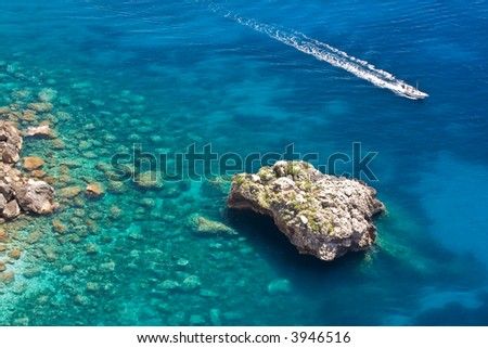 Rocky coastline in Capri.  Sea surface with rocks and a boat. - stock photo