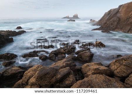 Rocky Coastline - Seal Rock, Laguna Beach, CA. This image shows a typical Californian rocky coast. This photo was captured near Crescent Bay, Laguna Beach, California. In the distance is Seal Rock. - stock photo