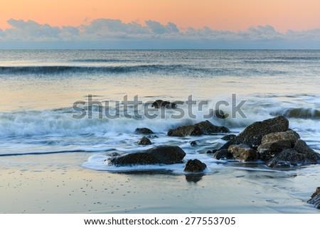 Rocky coastline where the Atlantic Ocean meets the shore at Folly Beach in Charleston, South Carolina. - stock photo