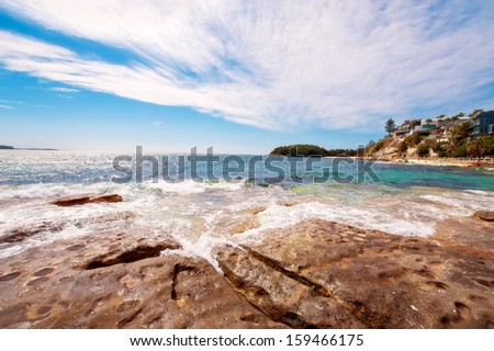 rocky coastline with blue sky and clouds crashing waves