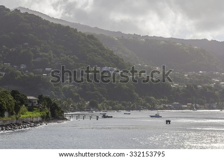 Rocky coastline with hills, pier and a boat in Roseau, on Caribbean island Dominica. - stock photo