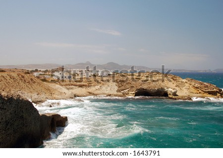 rocky coastline with sweet village in the distance in Milos island Greece - stock photo
