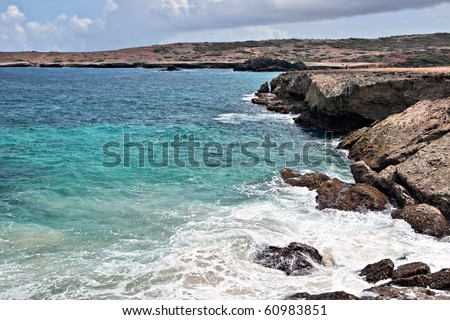 Rocky coastline with waves breaking on rocks.  Tropical Island in Caribbean Sea. - stock photo