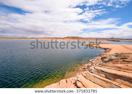Rocky Desert Lake - White clouds rolling over remote high desert lake. - stock photo
