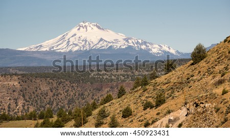 Rocky desert like landscape stands in the foreground near Mt Jefferson on Warm Springs Reservation - stock photo