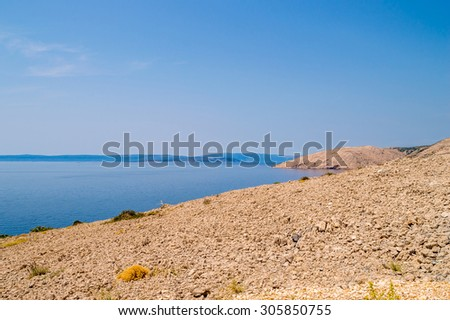 Rocky deserted coastal landscape of the island of Krk, Croatia, with the island Cres in the background, and the view of the Adriatic sea at the Mediterranean