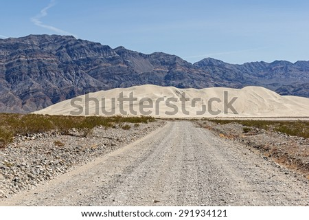 rocky dirt road leading to Eureka Dunes in Death Valley National Park - stock photo