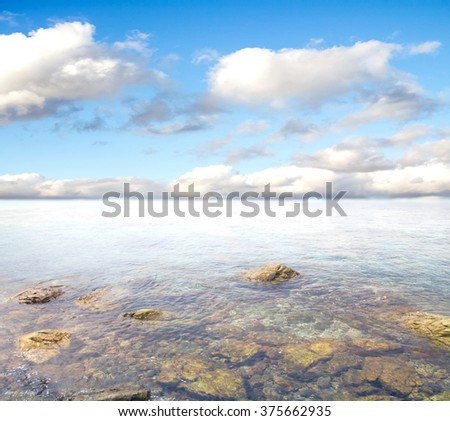 rocky entrance to the sea on a background of blue sky with clouds