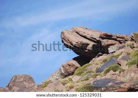Rocky formation sticking out of the mountain - stock photo