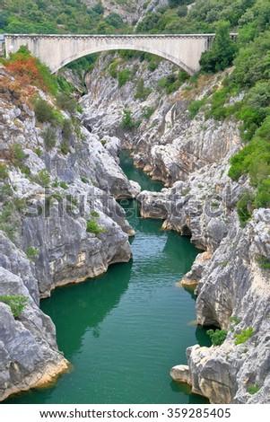 Rocky gorge and river under a stone bridge in Saint Guilhem le Desert, Languedoc Roussillon, France - stock photo
