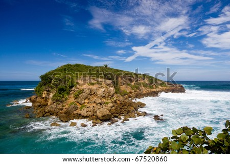 Rocky island in surf off the north east coast of Puerto Rico - stock photo