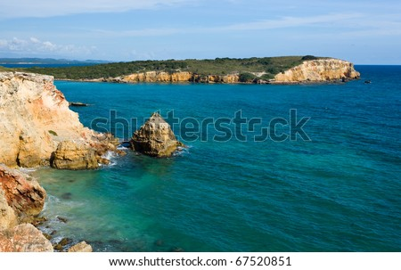 Rocky island in surf off the south west coast of Puerto Rico by Los Morillos Lighthouse - stock photo