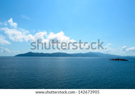 Rocky island in the distance over the beautiful blue sea - stock photo