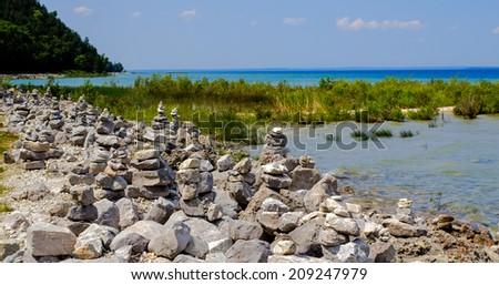 Rocky lakeshore with hundreds of zen-like rock structures left behind by tourists.  Mackinaw Island, Michigan.
