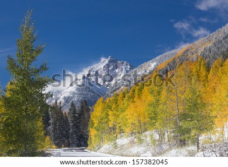 Rocky Mountain Covered in Fresh Snow Following a Passing Storm With Golden Aspen Trees - stock photo