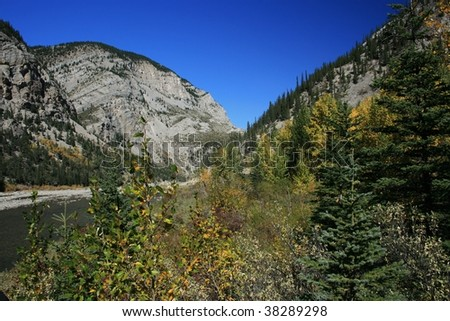Rocky mountain outlined against bright blue sky; fall foliage in foreground; river between; Oldman River, Alberta, Canada - stock photo