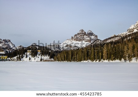 Rocky mountain peaks of Tre Cime over frozen Lake Misurina in the Dolomites, Italian Alps - wide panoramic view - stock photo