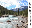 Rocky mountains and river with a rapids flowing in a valley between mountain wood in Jasper National Park (Alberta, Canada) - stock photo