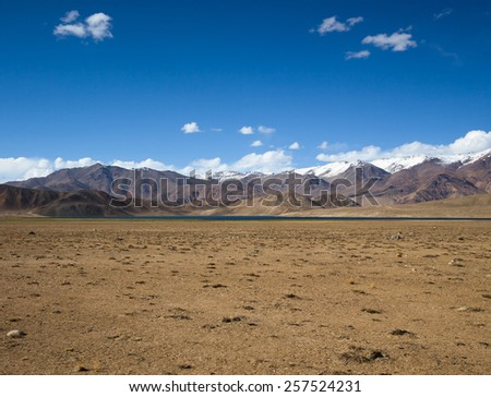 Rocky mountains and scorched valley on a background of blue sky with a few white clouds. Toned. - stock photo
