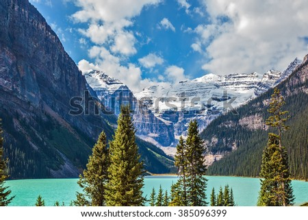Rocky Mountains, Canada, Banff National Park. Magnificent Lake Louise is surrounded by mountain peaks and glaciers. Great sunny day - stock photo