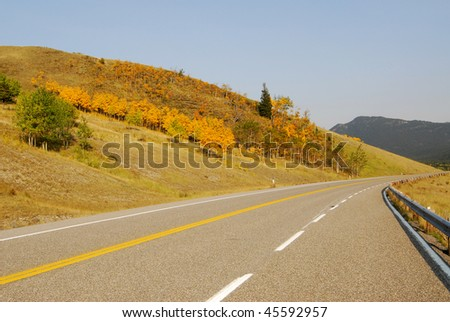 rocky mountains, forests and road (highway 40) while traveling in kananaskis country, alberta, canada - stock photo