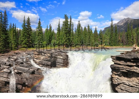Rocky mountains landscape with Athabasca River waterfall in Jasper National Park. (Alberta, Canada).  - stock photo
