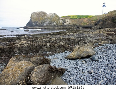 Rocky ocean beach with lighthouse in background - stock photo