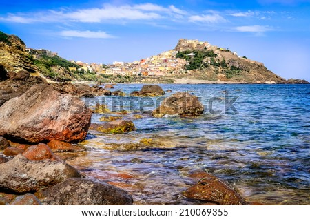 Rocky ocean coastline with colorful town Castelsardo, Sardinia, Italy - stock photo