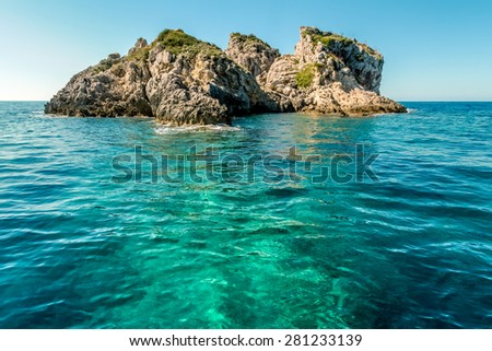 Rocky outcrop, an islet in shallow Ionian sea off the coast of Corfu, near Paleokastitsa. Emerald and turquoise waters and mediterranean sun. - stock photo