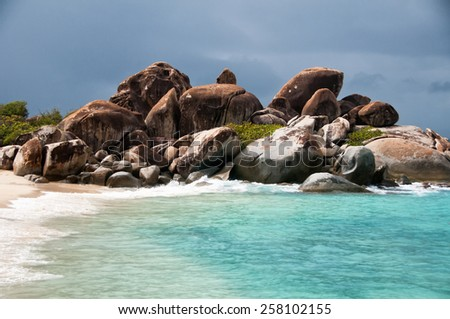 Rocky outcrop on a sandy beach with a calm blue sea and golden sand symbolic of a summer vacation in the tropics - stock photo