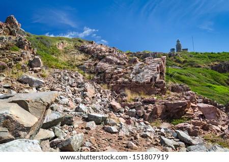 Rocky panorama landscape with coast lighthouse - stock photo