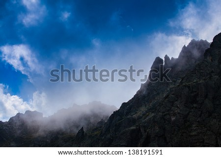 Rocky peaks and edges in the French Alps, and storm clouds in summer