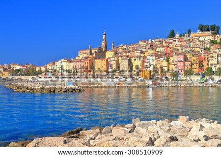 Rocky pier and distant buildings of Menton, French Riviera, France
