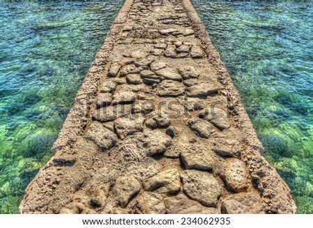 rocky pier surrounded by emerald water. Processed for hdr tone mapping effect. - stock photo
